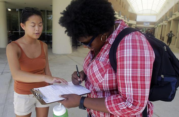 Aubrey Marks, left, helps a University of Central Florida student to register to vote in Orlando, Fla. in 2012. (Photo: John Raoux/AP)
