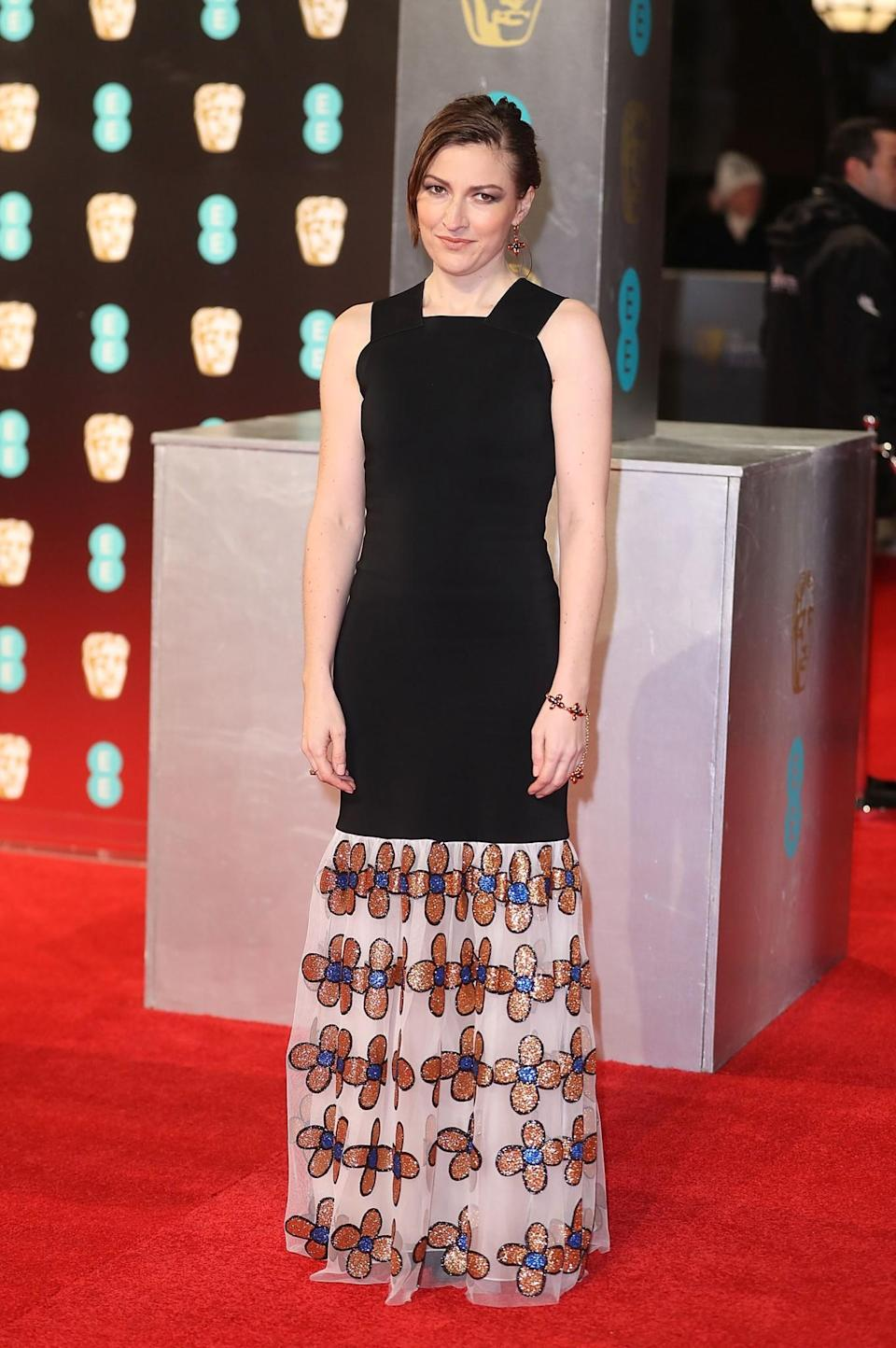 <p>Kelly chose a simple black dress with a shimmering floral hem. <i>[Photo: Getty]</i> </p>
