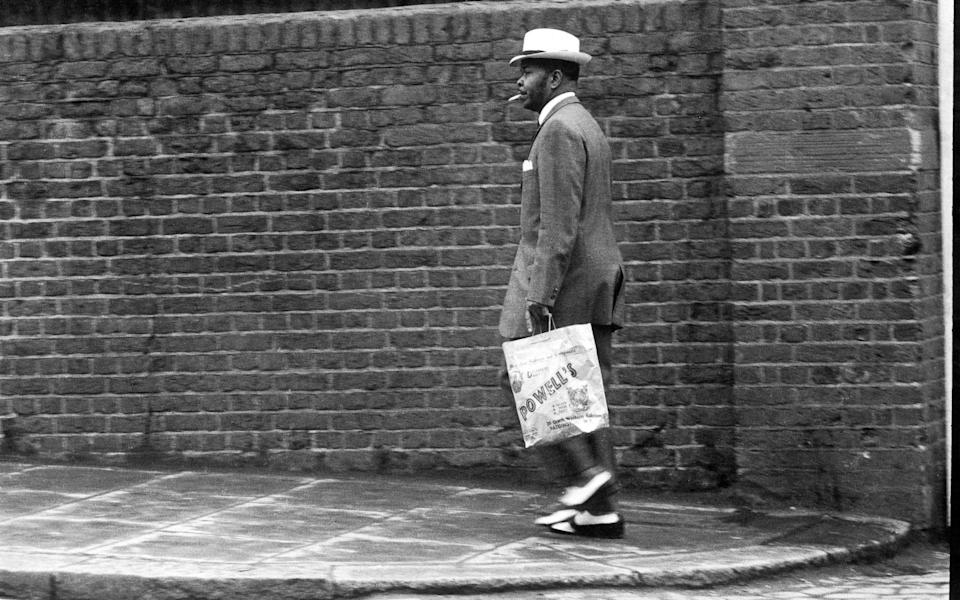 A man fashionably dressed in a zoot suit walking down Great Western Road, Notting Hill, London, 1968. (Photo by Charlie Phillips/Getty Images)  - Getty