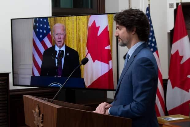 Prime Minister Justin Trudeau looks at a television screen as he listens to U.S. President Joe Biden speak during a virtual joint statement following a virtual meeting in Ottawa on February 23, 2021. (The Canadian Press - image credit)
