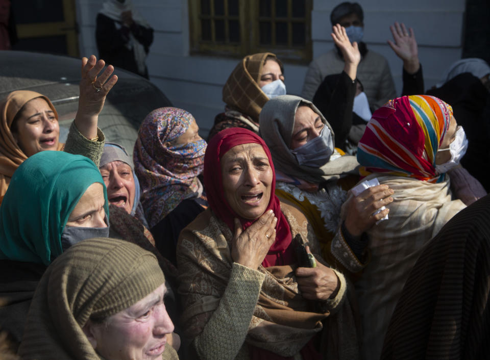 Relatives and family members cry near the coffin of Basharat Ahmad Zargar in Srinagar, Indian-controlled Kashmir, Sunday, Feb.14, 2021. Zargar, who was working at a power project, was among the dozens killed after a part of a Himalayan glacier broke off on February 7 sending a devastating flood downriver slamming into two hydropower projects in northern India. (AP Photo/Mukhtar Khan)