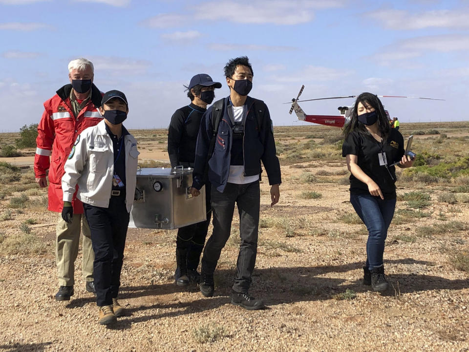 In this photo provided by the Australian Space Agency, members of the Japan Aerospace Exploration Agency (JAXA) arrive at a range support facility in Woomera, Australia, Sunday, Dec. 6, 2020, carrying a box containing asteroid samples that they retrieved on a remote area in southern Australia. JAXA said Hayabusa2 released the small capsule of samples Saturday. JAXA officials said they hoped to conduct a preliminary safety inspection at an Australian lab and bring the capsule back to Japan soon. (Australian Space Agency via AP)