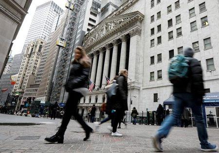 FILE PHOTO: People walk on Wall St. in front of the NYSE in New York