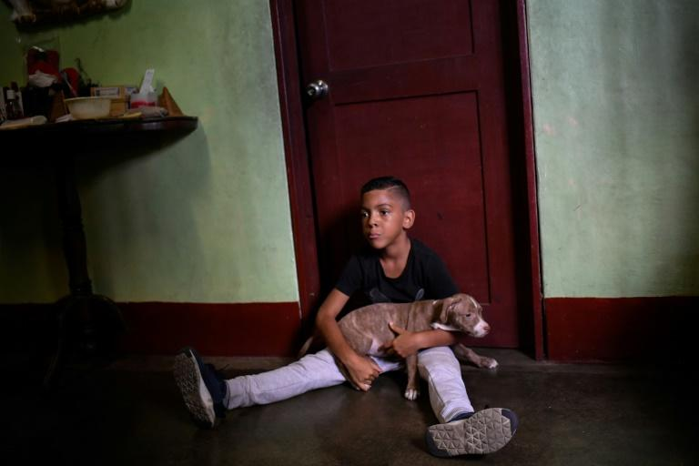 Venezuelan Fraiber Hernandez, eight, whose parents emigrated to Peru, plays with his dog in the Catia neighborhood in Caracas