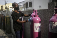 A worker from a private medical service brings oxygen bottles to aid the recovery of a COVID-19 patient, at her home in Lagos, Nigeria on Saturday, Feb. 6, 2021. A crisis over the supply of medical oxygen for coronavirus patients has struck nations in Africa and Latin America, where warnings went unheeded at the start of the pandemic and doctors say the shortage has led to unnecessary deaths. (AP Photo/Sunday Alamba)