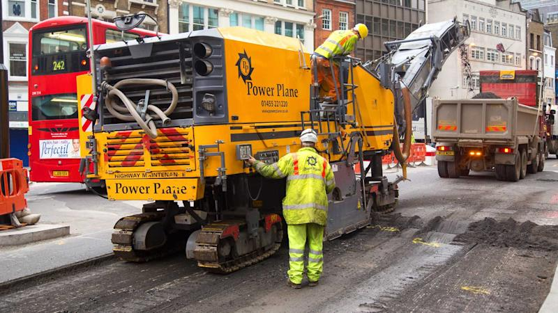 Workman using a cold milling machine in London