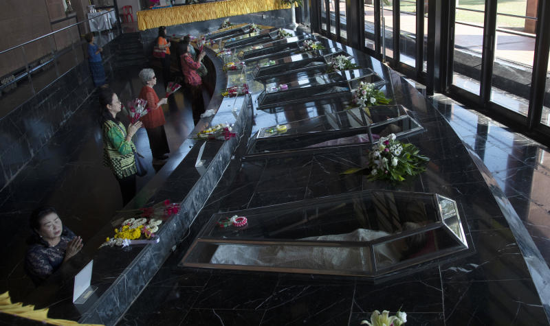 In this Saturday, Oct. 19, 2019, photo, Catholic devotees pray in front of glass caskets containing the seven replicas of the Blessed Martyrs at Christ Church, Songkhon village in Mukdahan province, northeastern Thailand. In 1940, seven villagers here were executed for refusing to abandon their Catholic faith, which Thai nationalists had equated with loyalty to France, whose colonial army in neighboring Indochina had fought Thailand in a brief border war. The seven were beatified in 1989 by Pope John Paul II, the first step to being named a saint. (AP Photo/Sakchai Lalit)