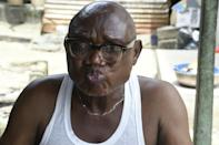 Kingdom Adugbo delivers his verdict after sipping from a glass of ogogoro (AFP/PIUS UTOMI EKPEI)
