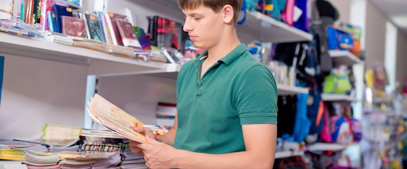 The young man buys a notebook in the store