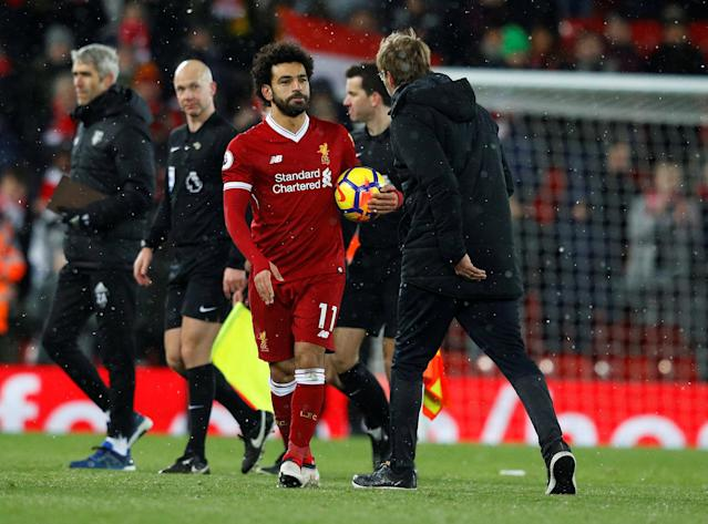 "Soccer Football - Premier League - Liverpool vs Watford - Anfield, Liverpool, Britain - March 17, 2018 Liverpool's Mohamed Salah celebrates with the match ball after the match REUTERS/Phil Noble EDITORIAL USE ONLY. No use with unauthorized audio, video, data, fixture lists, club/league logos or ""live"" services. Online in-match use limited to 75 images, no video emulation. No use in betting, games or single club/league/player publications. Please contact your account representative for further details."