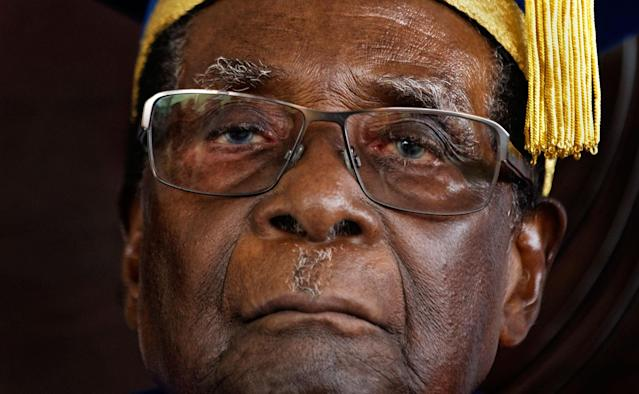 <p>Mugabe sits for formal photographs with university officials after presiding over a graduation ceremony at Zimbabwe Open University, Nov. 17, 2017. Mugabe made his first public appearance since the military put him under house arrest earlier that week. (Photo: Ben Curtis/AP) </p>