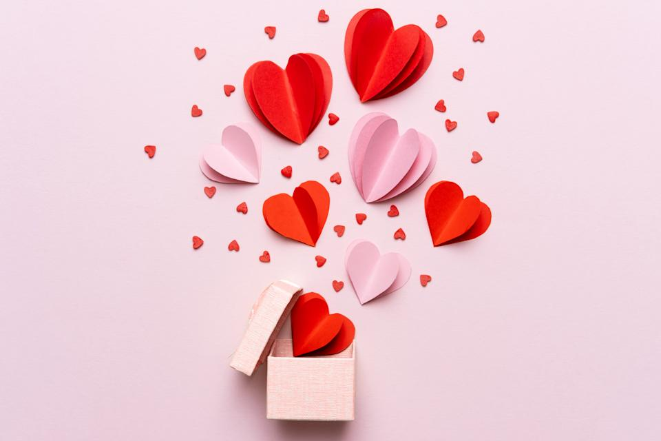 Valentine day composition with gift box and red hearts, photo template on pink background.