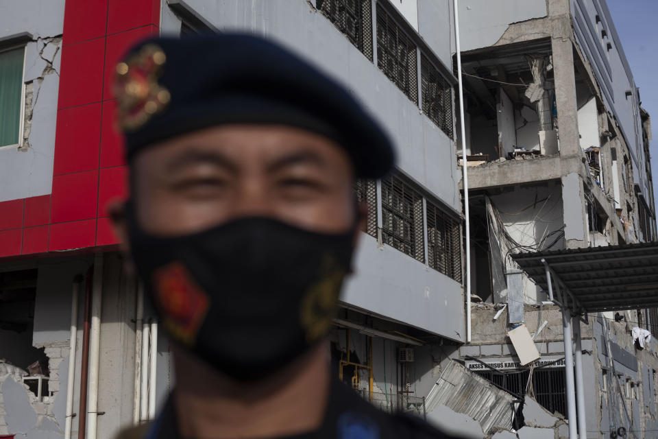 A police officer stands guard outside a shopping mall damaged in Friday's earthquake in Mamuju, West Sulawesi, Indonesia, Monday, Jan. 18, 2021. Aid was reaching the thousands of people left homeless and struggling after an earthquake that killed a number of people in the province where rescuers intensified their work Monday to find those buried in the rubble. (AP Photo/Yusuf Wahil)