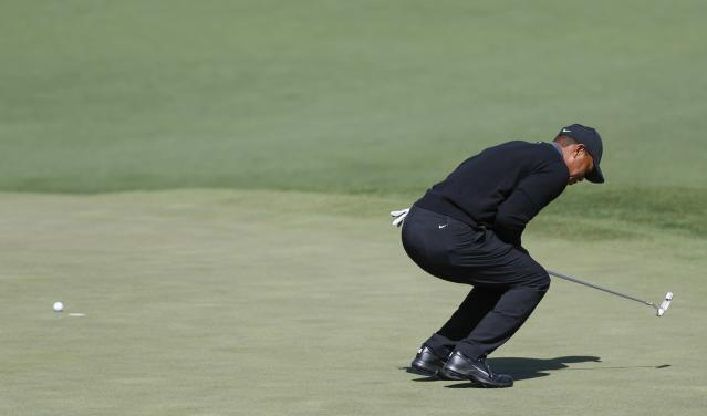 Tiger Woods reacts after missing a putt on the second hole during the first round at the Masters golf tournament. (AP)