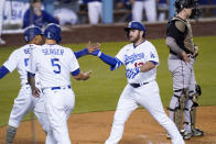 Los Angeles Dodgers' Max Muncy, second from right, is congratulated by Mookie Betts, left, and Corey Seager, second from left, after hitting a three-run home run as Miami Marlins catcher Chad Wallach stands at the plate during the second inning of a baseball game Friday, May 14, 2021, in Los Angeles. (AP Photo/Mark J. Terrill)
