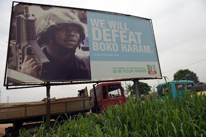 A campaign signboad displayed by the ruling All Progressives Congress to show its readiness to defeat Boko Haram Islamists in Ogijo, Nigeria, on July 3, 2015 (AFP Photo/Pius Utomi Ekpei)