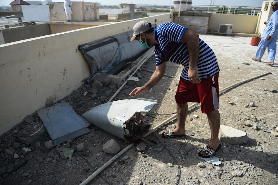 A man checks a part of a Pakistan International Airlines aircraft after it crashed in a residential area in Karachi on May 22, 2020. - A Pakistani plane with nearly 100 people on board crashed into a residential area in the southern city of Karachi on May 22, killing several people on the ground. (Photo by Rizwan TABASSUM / AFP) (Photo by RIZWAN TABASSUM/AFP via Getty Images)