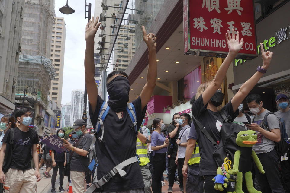 "Protesters gesture with five fingers, signifying the ""Five demands - not one less"" as they march along a downtown street during a pro-democracy protest against Beijing's national security legislation in Hong Kong, Sunday, May 24, 2020. Hong Kong's pro-democracy camp has sharply criticised China's move to enact national security legislation in the semi-autonomous territory. They say it goes against the ""one country, two systems"" framework that promises the city freedoms not found on the mainland. (AP Photo/Vincent Yu)"