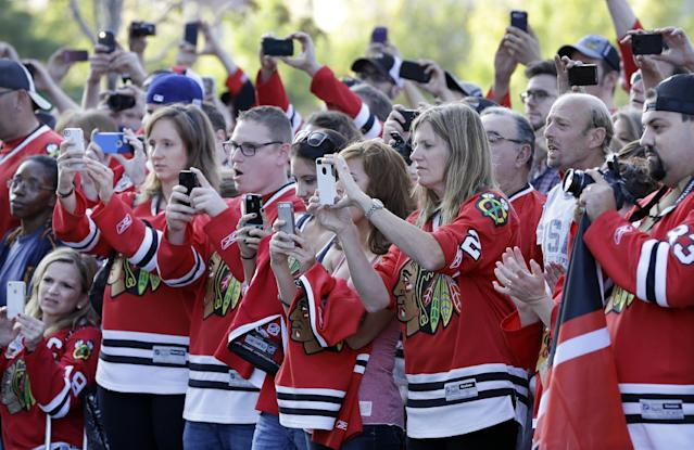 Fans take photos during a special red carpet event in front of the United Center as the Chicago Blackhawks arrive for their season-opener NHL hockey game against the Washington Capitals Tuesday, Oct. 1, 2013, in Chicago. (AP Photo/Nam Y. Huh)