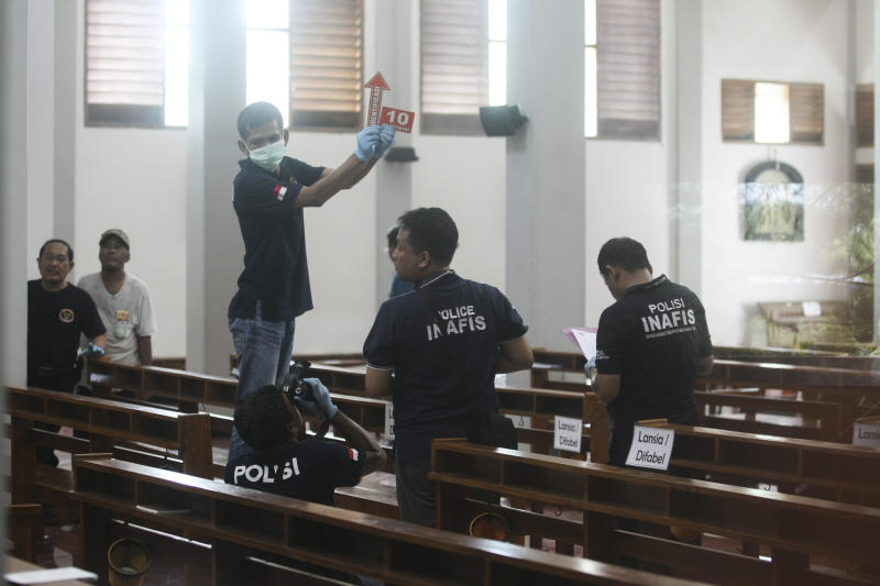 In this image shot through a glass window, police investigators examine the interior of St. Lidwina Church following an attack in Sleman, Yogyakarta province, Indonesia, Sunday, Feb. 11, 2018. Police shot a sword-wielding man who attack the church during a mass, injuring a number of people including a German priest. The reason for the attack Sunday morning was not immediately clear. (AP Photo)