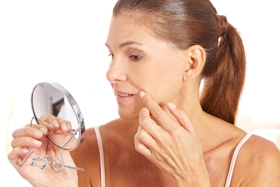 woman holding a mirror up checking her skin, changes over 40