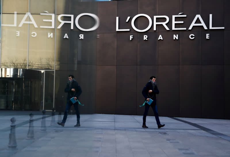 A man walks by the logo of French cosmetics group L'Oreal in the western Paris suburb of Levallois-Perret