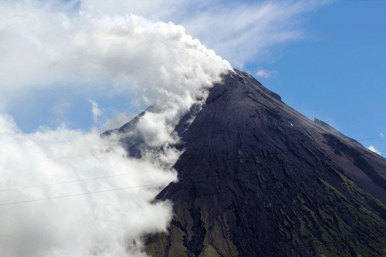 Mount Mayon spews a thick column of ash into the air on May 7, 2013, as seen from Albay province in the Philippines. Three German tourists and their Filipino tour guide were crushed to death when the volcano spewed a giant ash cloud and a hail of rocks on Tuesday, authorities said