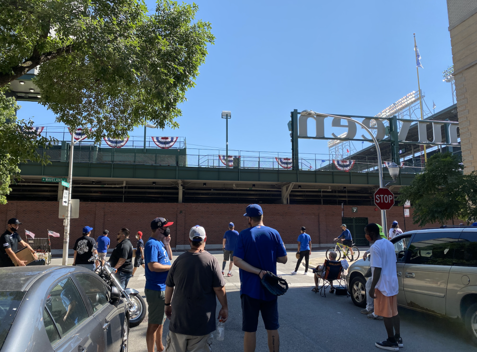 Fans wait out on Waveland Avenue for a ball to fly over the left field fence at Wrigley Field. (Yahoo Sports)