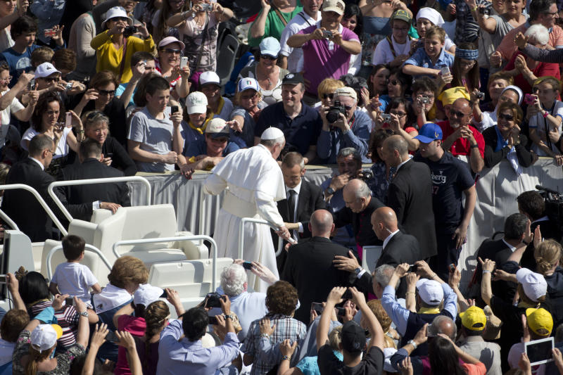 Pope Francis steps out of his pope-mobile to greet faithful and walk the last part of his way to the altar to deliver his weekly general audience in St. Peter's Square at the Vatican, Wednesday, May, 8, 2013. (AP Photo/Andrew Medichini)