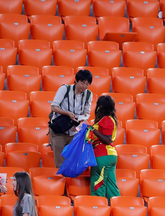 Soccer Football - World Cup - Group H - Japan vs Senegal - Ekaterinburg Arena, Yekaterinburg, Russia - June 24, 2018 Senegal and Japan fans clean up after themselves after the match REUTERS/Andrew Couldridge