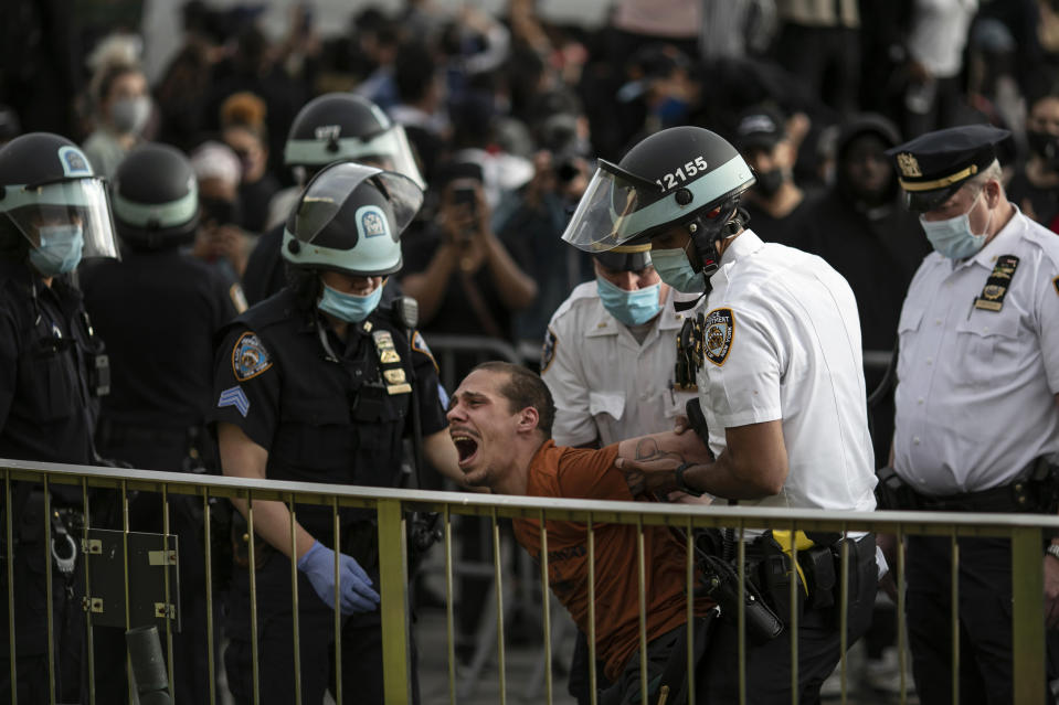 FILE — In this June 1, 2020 file photo, New York City Police officers arrest a man during a solidarity rally calling for justice over the death of George Floyd, in the Brooklyn borough of New York. The New York Police Department was caught off guard by the size and scope of the spring protests sparked by the police killing of George Floyd in Minneapolis and resorted to disorder control tactics that stoked tensions and stifled free speech rights, the city's inspector general said in a report released Friday, Dec. 18, 2020. (AP Photo/Wong Maye-E, File)