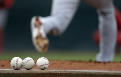 Balls sit on a ledge as St. Louis Cardinals pitcher Austin Gomber delivers a pitch while throwing a bullpen session at spring training baseball practice Wednesday, Feb. 13, 2019, in Jupiter, Fla. (AP Photo/Jeff Roberson)