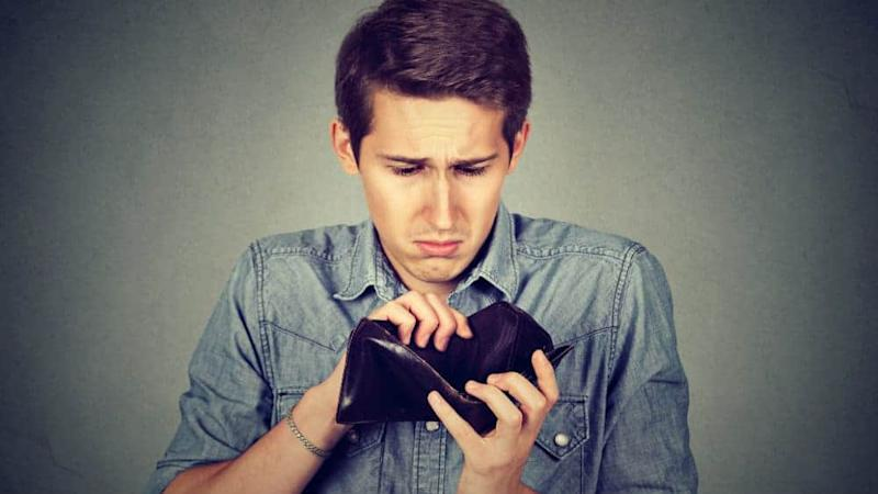 Man with no money. Businessman holding empty wallet