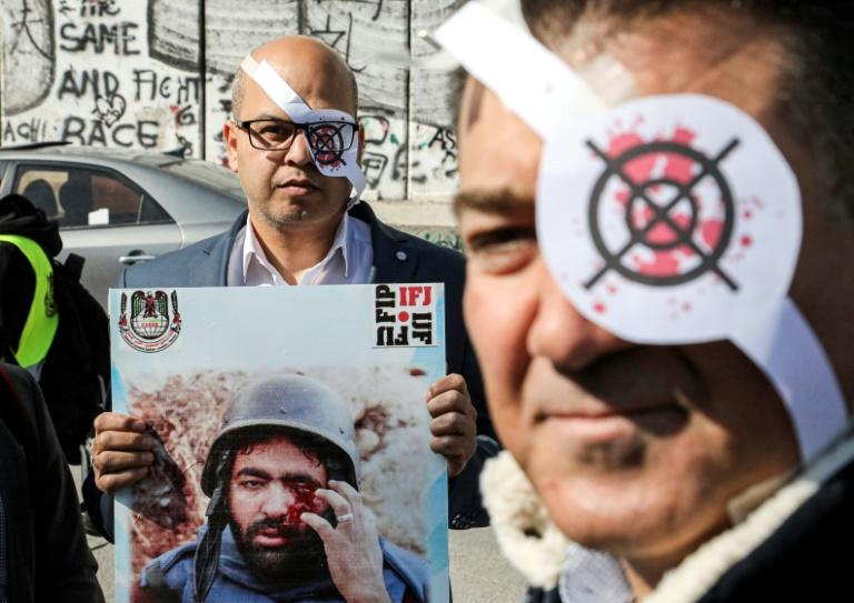 Palestinian journalists -- many wearing eye patches -- demonstrate by the Israeli barrier in Bethlehem in the occupied West Bank against the wounding of a colleague (AFP Photo/HAZEM BADER)