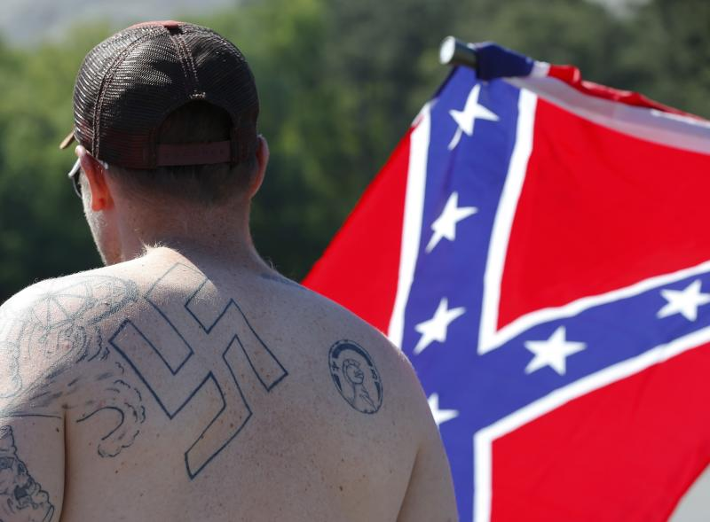 FILE - In this April 23, 2016 file photo, a man walks during a protest at Stone Mountain Park, in Stone Mountain, Ga. Extremist groups are joining together with a shared goal for whites. A new Ku Klux Klan alliance formed in March 2017 has united chapters from around the country, and a consortium of organizations composed of white nationalists and white separatists is marking its first anniversary. Watchdog groups say white extremists typically can't work together because of jealousy and infighting. But leaders say they're united as never before. (AP Photo/John Bazemore)