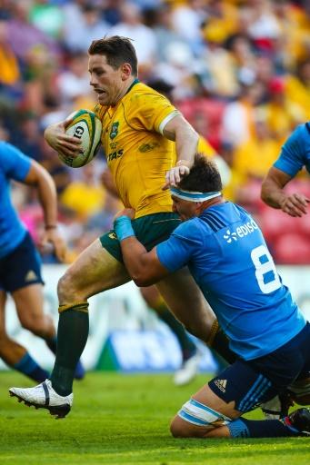 Bernard Foley of Australia is tackled by Andries Van Schalkwyk of Italy during their rugby union Test match, at Suncorp Stadium in Brisbane, on June 24, 2017