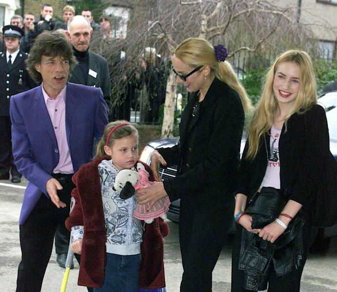 FILE - This March 20, 2000 file photo shows British pop star Mick Jagger arriving at his old school in Dartford, east of London, to open a new music center with his former wife Jerry, second from right, and children, Elizabeth, right, and Georgia, at front. Jagger is the new spokesmodel for Material Girl, the collection designed by Madonna and her daughter Lola. (AP Photo)