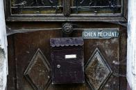 """A letter box and a """"Beware of the dog"""" sign are seen on a gate to an abandoned house. (Reuters)"""