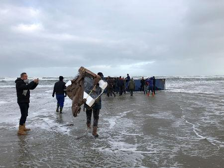 A person carries a flat-screen television set as others inspect a cargo container after it washed up on a beach in Terschelling, Netherlands January 2, 2019 in this image obtained from social media. Erik Scheer via REUTERS