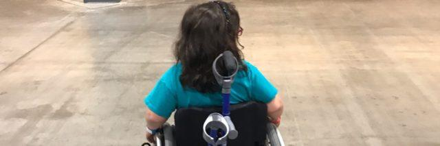 view of the back of a girl in a wheelchair, crutches attached to chair