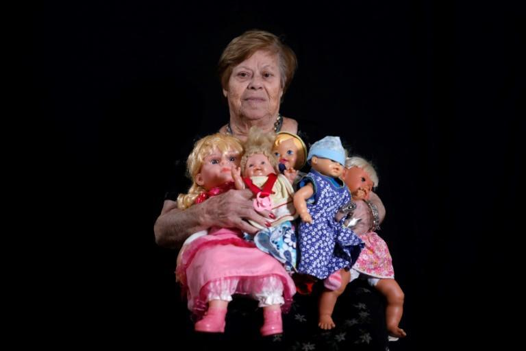 Malka Zaken, 91, says being with her dolls reminds her of being a child at home when her mother used to buy her dolls (AFP Photo/MENAHEM KAHANA)