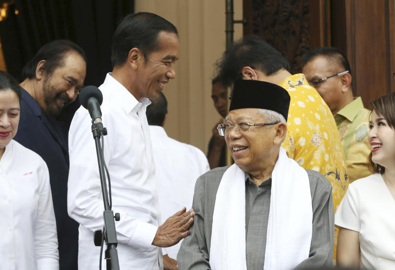 Incumbent Indonesian President Joko Widodo, center left, shares a light moment with his running mate Ma'ruf Amin, center right, during a press conference after a meeting with their coalition parties in Jakarta, Indonesia,, Thursday, April 18, 2019. Widodo said Thursday he was won reelection after securing an estimated 54% of the vote, backtracking on an earlier vow to wait for official results after his challenger made improbable claims of victory. (AP Photo/Achmad Ibrahim)