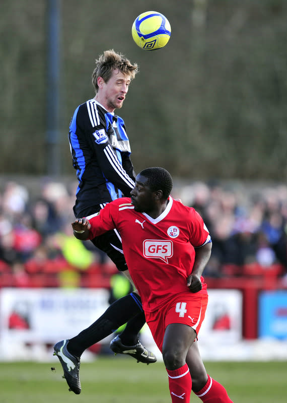 "Stoke City's striker Peter Crouch (L) vies with Crawley Town's defender Pablo Mills during their FA Cup fifth round football match against Crawley Town at Broadfield Stadium in Crawley, England on February 19, 2012. RESTRICTED TO EDITORIAL USE. No use with unauthorized audio, video, data, fixture lists, club/league logos or ""live"" services. Online in-match use limited to 45 images, no video emulation. No use in betting, games or single club/league/player publications. (Photo by Glyn Kirk/AFP/Getty Images)"