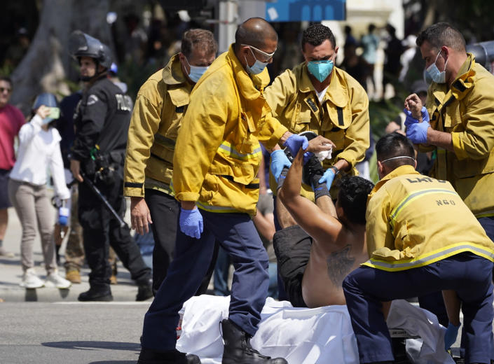 Los Angeles Fire department paramedics removed an injured demonstrator, who was stabbed in the chest during clashes between anti-vaccination demonstrators and counter-protesters during an anti-vaccination protest in front of the City Hall in Los Angeles on Saturday, Aug. 14, 2021. A man was stabbed and a reporter was attacked Saturday at a protest against vaccine mandates on the south lawn of Los Angeles' City Hall after a fight broke out between the protesters and counter-protesters, the Los Angeles Police Department and local media said. ( AP Photo/Damian Dovarganes)
