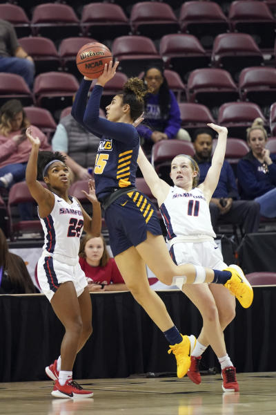 UNC Greensboro Nadine Soliman (35) drives the ball to the basket between Samford Raven Omar (22) and Paige Serup (11) in the first half of an NCAA women's college basketball game for the Southern Conference championship tournament, Sunday, March 8, 2020, in Asheville, N.C. (AP Photo/Kathy Kmonicek)