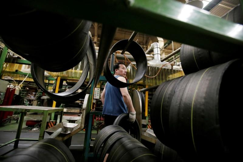 FILE PHOTO: An employee works on the production line of a tyre factory under Tianjin Wanda Tyre Group in Xingtai