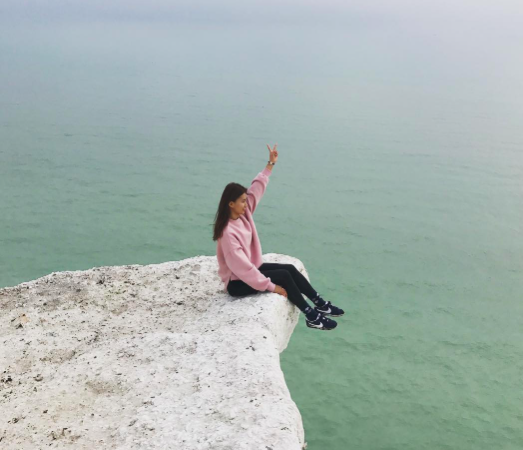 Risky: The tourists sat right on the edge of the cliff (Instagram)