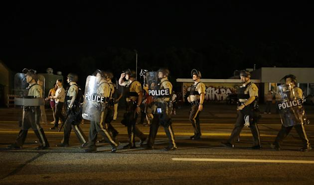 Police walk around protesters as people gather along West Florissant Avenue in Ferguson, Mo., Tuesday. (AP Photo/Jeff Roberson)