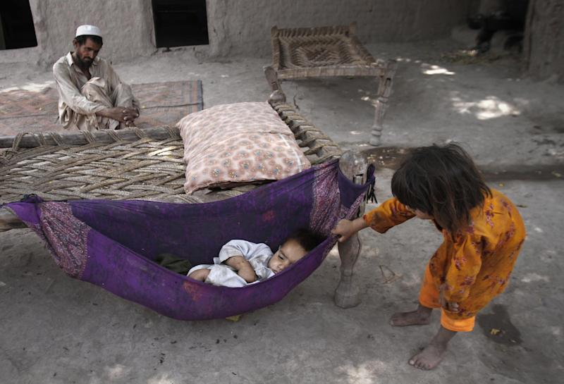 In this Thursday, June 28, 2012 photo, Razi Khan, background, looks at Irshad, 2, sleeping in a hammock attached to a bed at her home in Surkh Rod, district of Nangarhar east of Kabul, Afghanistan. For Khan, a debt of almost $ 900 has condemned him and his family to years of work in a brick factory. With a salary of just $ 6 a day to feeds his eight children and sick wife, it is unlikely that he will soon pay off the debt that has followed him for the past six years. (AP Photo/Rahmat Gul)
