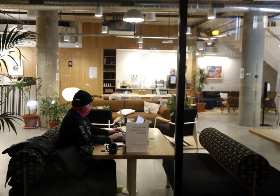 A man wearing a face mask works in his computer at a coffee shop downtown Prague, Czech Republic, Tuesday, Oct. 13, 2020. The Czech Republic is imposing a new series of restrictive measures in response to a record surge in coronavirus infections. Prime Minister Andrej Babis says that all bars, restaurants and clubs will be closed, starting on Wednesday Oct. 14, 2020, while drinking of alcohol is banned at public places.(AP Photo/Petr David Josek)